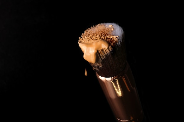 Liquid foundation lying on the make up brush for contouringfoundation beauty facial cosmetics