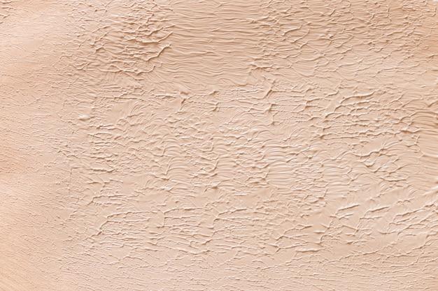 Liquid foundation texture background. neutral beige corrector. Premium Photo