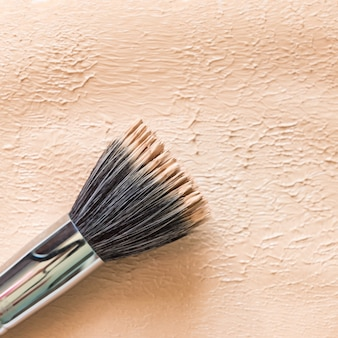 Liquid foundation texture background with duofibre brush. neutral beige corrector.