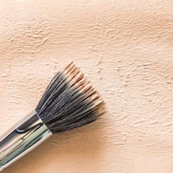 Liquid foundation texture background with duofibre brush. neutral beige corrector. Premium Photo