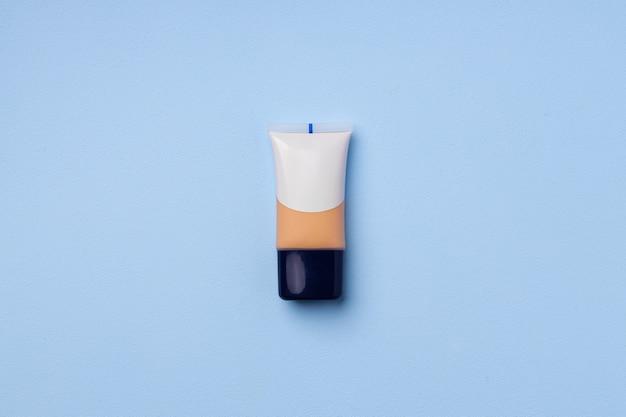 Liquid foundation tube on blue background close up photo