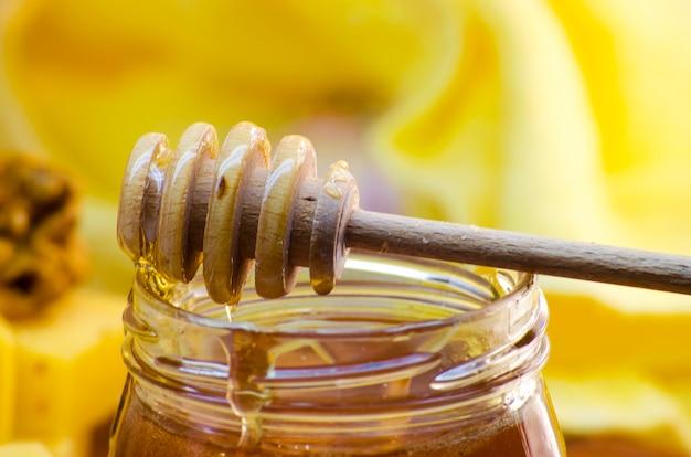 Жидкий мед в стеклянной банке с ковшиком для меда для нее