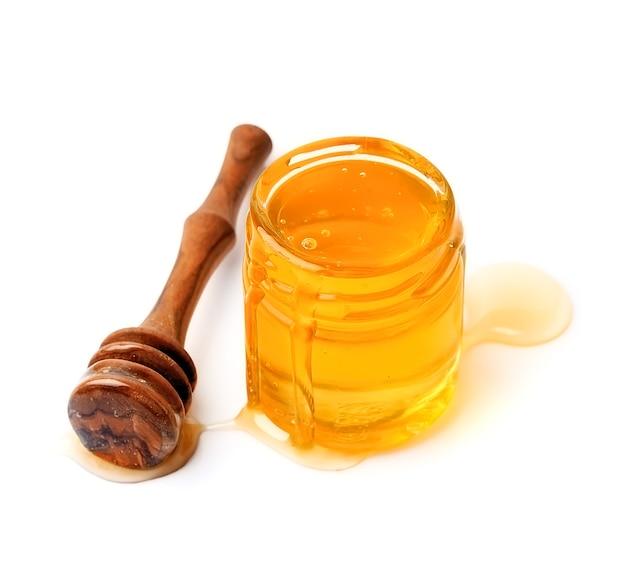 Жидкий мед на стеклянной банке, изолированные на белом фоне.