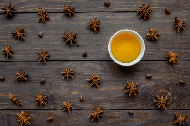 Liquid honey in a plate and star anise on a dark wooden background