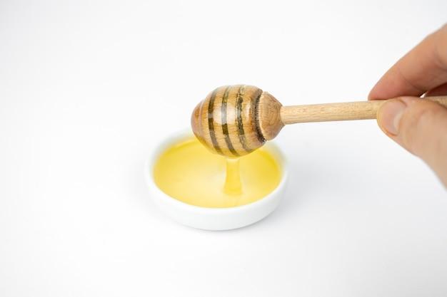 작은 흰색 접시에 나무 막대기로 붓는 액체 꿀