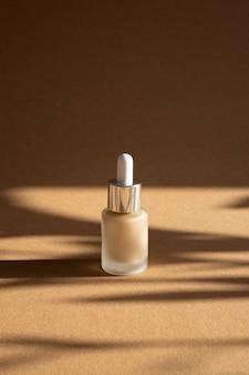 暗い影、モダンなモックアップコンセプトsidrビューと茶色の背景にガラス瓶の液体メイクアップファンデーション