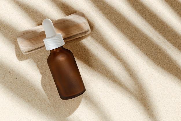 야자수 잎의 햇빛과 그림자가 있는 모래 위의 어두운 유리 병에 액체 제품 포장