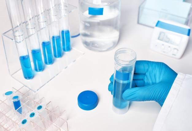 장갑을 낀 여성 손의 액체 샘플, 유리 및 플라스틱 튜브의 파란색 액체 샘플