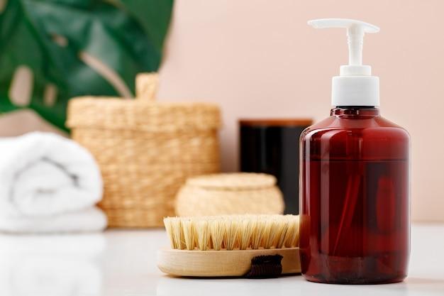 Liquid soap container and massage brush in bathroom close up