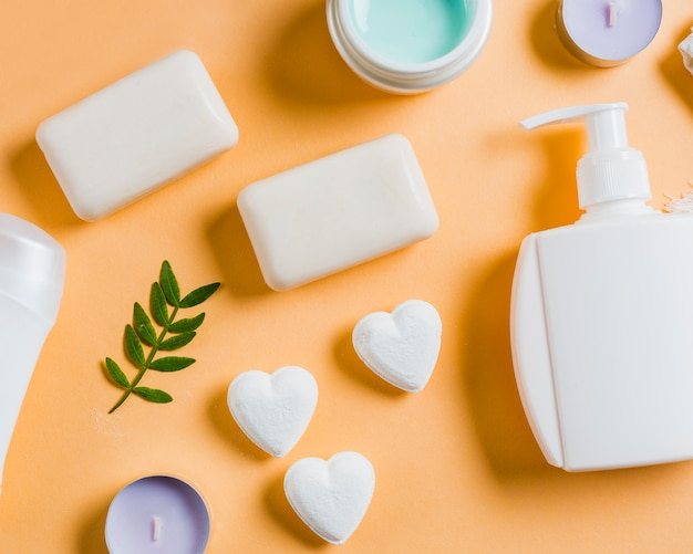 Liquid soap dispenser pump; soap and cream on colored backdrop