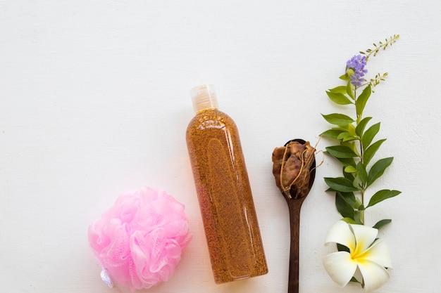 花と黒いスプーンの近くの液体石鹸