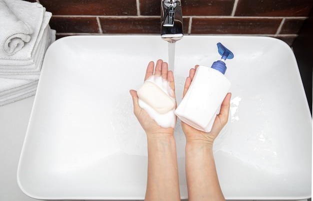 Liquid soap and solid soap in female hands top view. concept of personal hygiene and health.