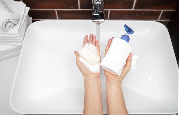 Liquid soap and solid soap in female hands top view.. the concept of personal hygiene and health.