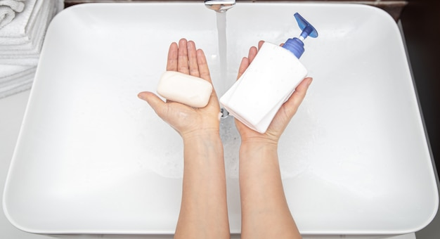 Liquid soap and solid soap in female hands top view..  personal hygiene and health.