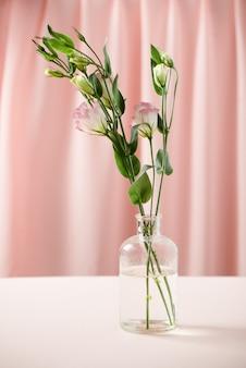 ピンクの背景にボトルのトルコギキョウの花。母の日、誕生日、バレンタインデー、女性の日、お祝いのコンセプト。テキスト用のスペース。