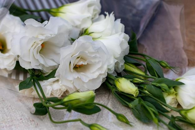 トルコギキョウの白い花束がテーブルの上にあります。