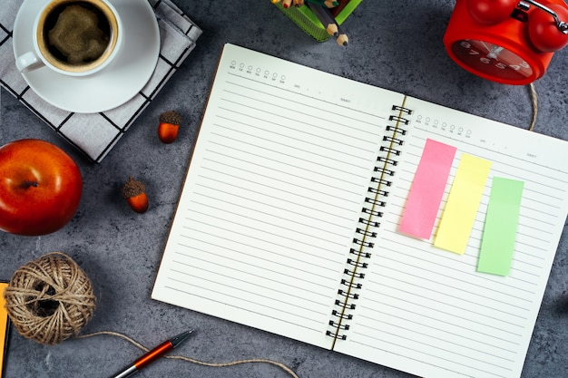 To do list concept. blank notebook with coffee cup, red clock, and pencil. top view, flat lay.