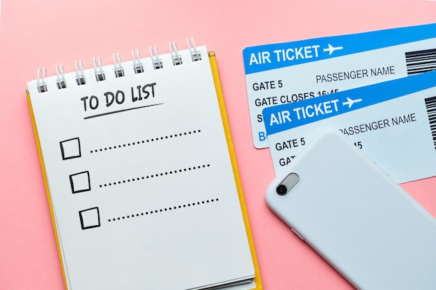 To do list concept on a notebook near tickets and a smartphone on a pink wall