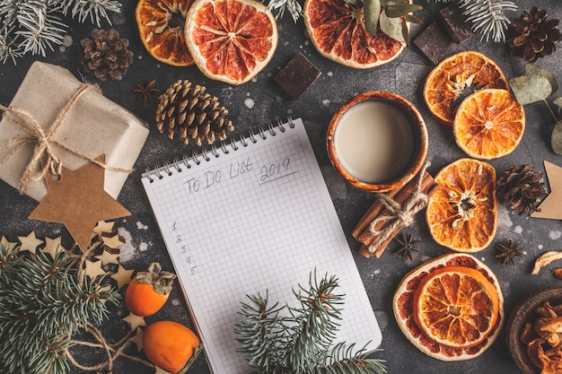 To do list for the new year on a dark background christmas decorations. christmas flat lay.