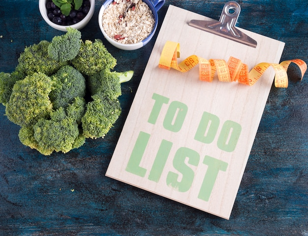 To do list with broccoli and measuring tape on table
