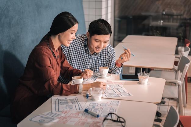 Внимательно слушать. темноволосый деловой партнер внимательно слушает своего коллегу во время обсуждения проекта