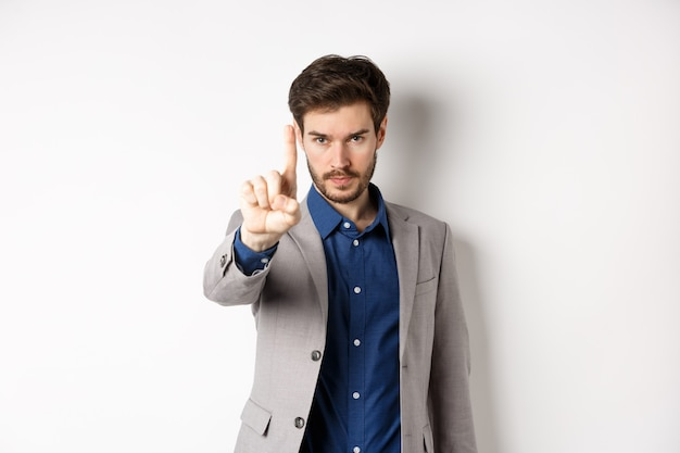 Listen to me. serious male ceo manager showing one finger, scolding or telling to stop, tell no, hold right there sign, standing on white background in suit.