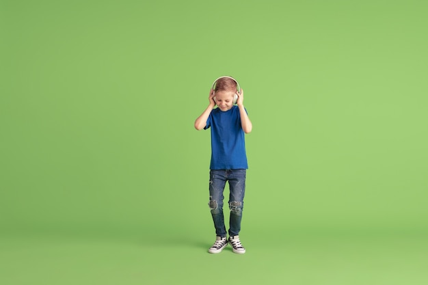 Listen to musi happy boy playing and having fun on green  wall. caucasian kid in bright looks playful, laughting, smiling. concept of education, childhood, emotions, facial expression.