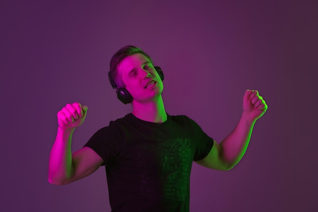 Listen to music, singing, enjoying. caucasian man's portrait on purple studio background in neon light. beautiful male model in black shirt. concept of human emotions, facial expression, sales, ad.