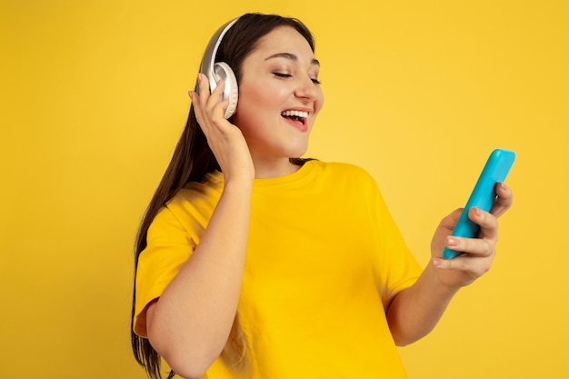 Listen to music with wireless headphones and phone. caucasian woman on yellow studio background. beautiful brunette model in casual. concept of human emotions, facial expression, sales, ad, copyspace.