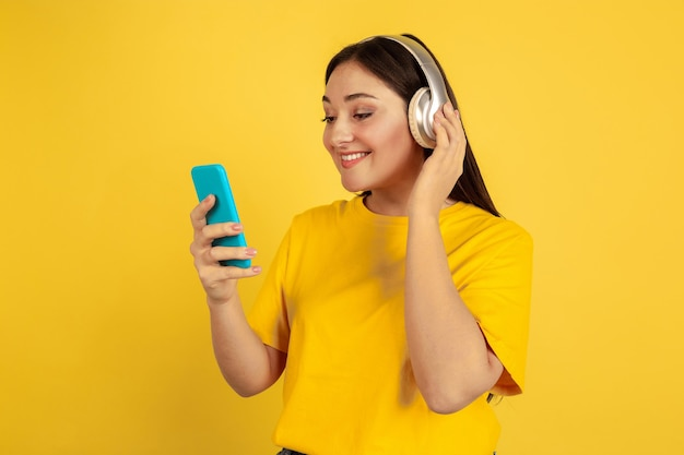 Listen to music with wireless headphones and phone. caucasian woman on yellow  wall. beautiful brunette model in casual. concept of human emotions, facial expression, sales, ad, copyspace.