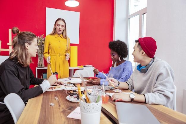 マネージャーの話を聞いてください。ファッション部門のマネージャーに耳を傾ける3人の有望なクリエイティブデザイナー