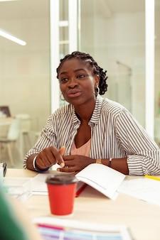 Послушай меня. симпатичная брюнетка-учительница сидит напротив своих учеников, тренируя разговорные навыки