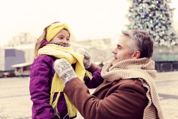 내 말 잘 들어. 그의 아이에게 스카프를 만드는 동안 긍정적 인 표현을 기쁘게 남자