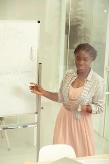 내 말 잘 들어. 그녀의 학생들과 이야기하는 동안 보드에 작업을 작성하는 예쁜 갈색 머리 여자