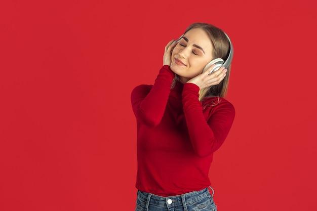 音楽を聴く。赤い壁に分離された若い白人の金髪女性の白黒の肖像画。