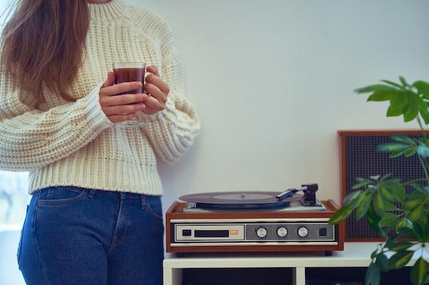 레코드가있는 빈티지 레트로 비닐 턴테이블에서 음악을 듣고 아늑한 시간을 즐기십시오.