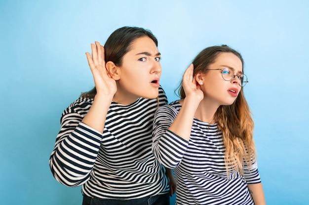 秘密を聞いてください。グラデーションの青い壁に孤立した若い感情的な女性。人間の感情、顔の表現、友情、広告の概念。カジュアルな服装の美しい白人モデル。