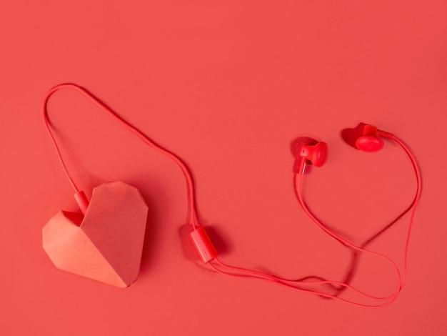 사랑의 음악을 들어라. 헤드폰과 밝은에 빨간 종이 심장