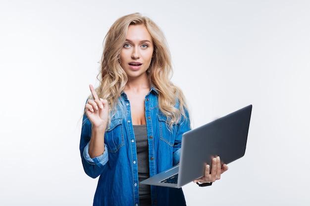 聞いて。ノートパソコンを持って指を上げて、灰色の背景に孤立して立っている間重要な発言をする美しい金髪の女性