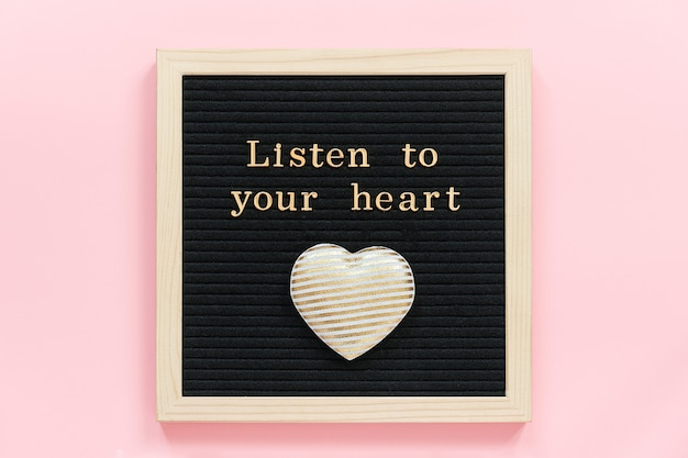 Listen to your heart. motivational quote in gold letters and decorative textile heart on black letter board on pink background.