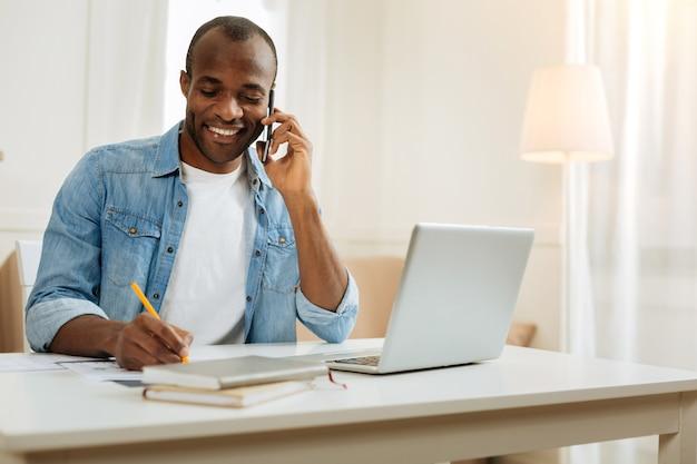 Прослушивание. привлекательный вдохновленный молодой афро-американский бизнесмен улыбается, разговаривает по телефону и пишет, сидя за столом и работая на своем ноутбуке