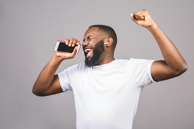 멋진 음악 듣기. 쾌활한 젊은 흑인 흑인 남자 춤 춤 회색 배경 위에 격리.