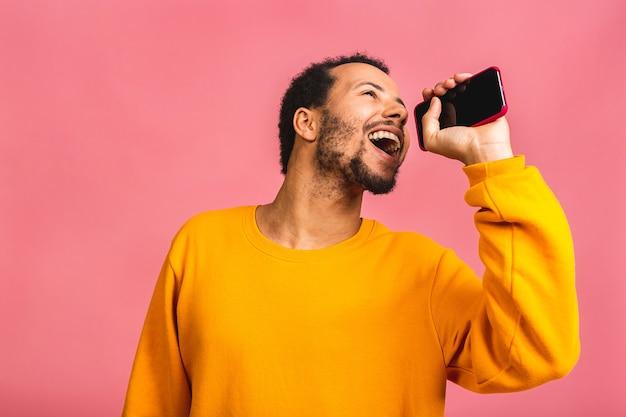 クールな音楽を聴きます。ピンクの上に孤立したダンスと歌を移動する若い陽気な男