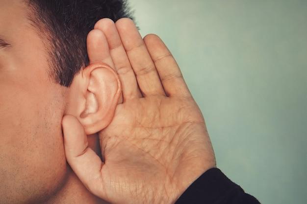 Слушающий самец держит руку возле уха. понятие глухоты или подслушивания. слабослышащих.