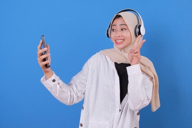 Прослушивание музыки и разговор по телефону в наушниках. молодой женский человек держит мобильный телефон