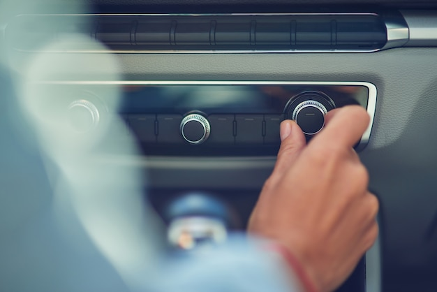 Слушая музыку, обрезанный снимок женщины, включающей радио во время вождения по городу, крупным планом