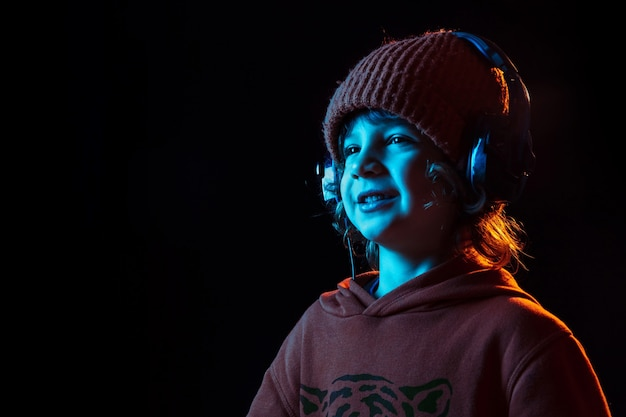 Listening to music and dancing. caucasian boy's portrait on dark  wall in neon light. beautiful curly model. concept of human emotions, facial expression, sales, ad, modern tech, gadgets.