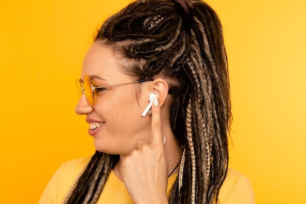 エアポッドで音楽を聴く。白いエアポッドを持つ黄色のスタジオの女性。 Premium写真
