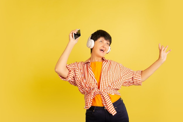 Listening to music with headphones. portrait of senior woman in stylish outfit on yellow studio wall