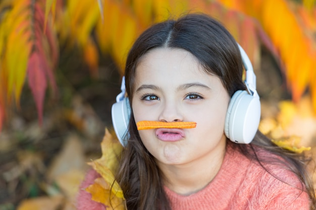 Listening song. autumn playlist concept. enjoy music outdoors fall warm day. audio file. educational podcast. feel joy. kid girl relaxing near autumn tree with headphones. music for autumn cozy mood.